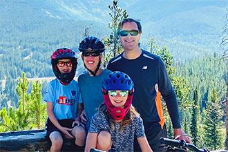 Riley and her family stop for a photo while mountain biking in the mountains